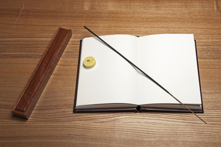 An opened brown vintage book and a piece of wood on a brown table isolated on brown background