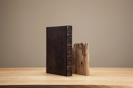 A vintage book and wood on a brown table isolated on brown background Stockfoto