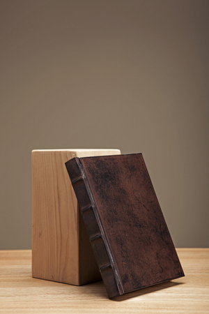 A brown vintage book and a piece of wood on a brown table isolated on brown background
