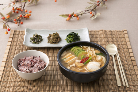 Delicious Korean food - kind of noodles, soup with rice and side dish with fish on the table. 069