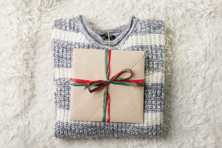 Objects photo for winter season. A Christmas present on a folded sweater on furry background