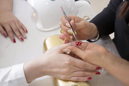Nail salon woman hands treatment. Nail saloon woman painting color nail polish in hands stock photo. 070 Stock Photo