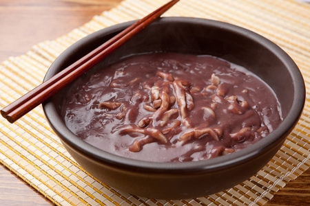 Korean handmade noodle kalguksu with red beans with chopsticks