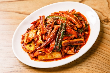 Spicy Korean food squid stir-fried, vegetables with spicy sauce Фото со стока