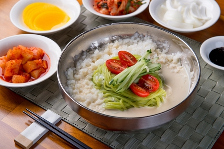 Korean cold noodle with soy soup with cucumber, tomatoes with kimchi side dishes, close-up shot