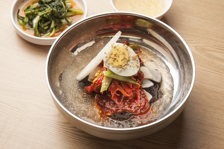 Korean cold noodles, naengmyeon with pollack, kodari, picked with chopsticks