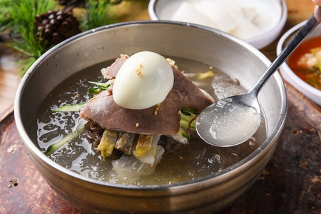 Korean food Cold Noodles with meat and vegetables, Mul-naengmyeon, scooped with spoon Stok Fotoğraf