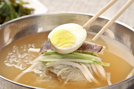 Korean food Cold Noodles with meat and vegetables, Mul-naengmyeon, picked with chopsticks Stok Fotoğraf