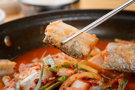 Korean spiced braised beltfish held with chopsticks