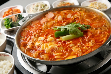 Spicy Korean sausage stew, budae jjigae made with vegetables, rice cake, ham, sasuage, baked beans, kimchi and gochujang with side dishes
