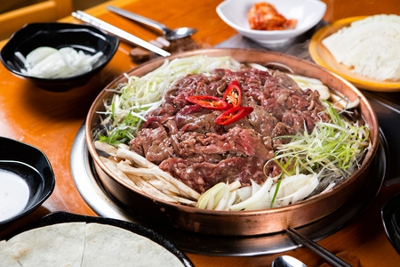 Korean cuisine Bulgogi, marinated beef barbecue with vegetables on grill 写真素材