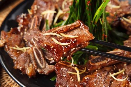 Korean-style braised short ribs, LA Galbi held with wooden chopsticks 写真素材