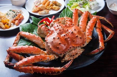 steamed whole King Crab on plate with garnish and side dishes