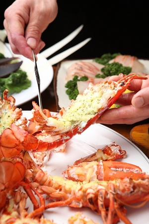 pulling out grilled lobsters meat using seafood fork Stock Photo