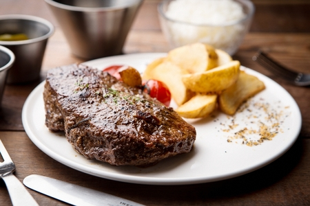 beef steak served with wedge potatoes and tomatoes Stock Photo