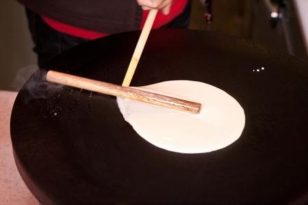 making crepe on crepe maker with wooden batter spreader stick Banco de Imagens