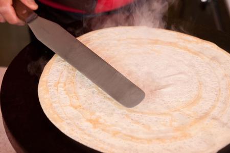 making crepe on crepe maker with steel batter spreader