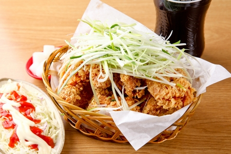 fried chicken with onion leeks in wooden basket served with cola and salad