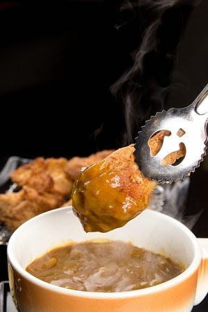 fried chicken leg dipped into curry sauce with tongs