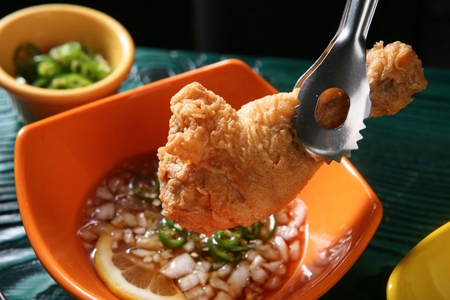 close-up shot of fried chicken leg held with tongs