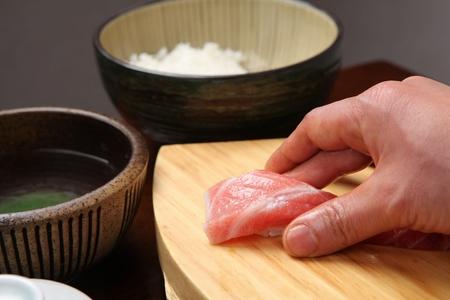 chef hand making tuna sushi on wooden board Stock Photo