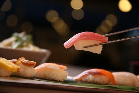 sushi set, focused on tuna sushi held using chopsticks Imagens