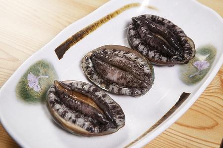 three raw abalones on plate Stock Photo