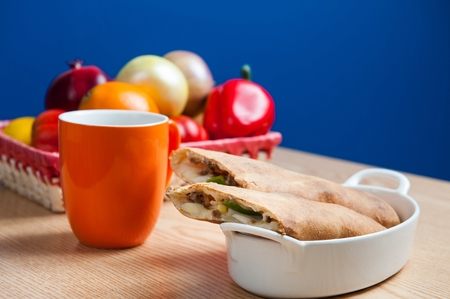 Barbecued beef quesadilla on a wooden table in a blue background