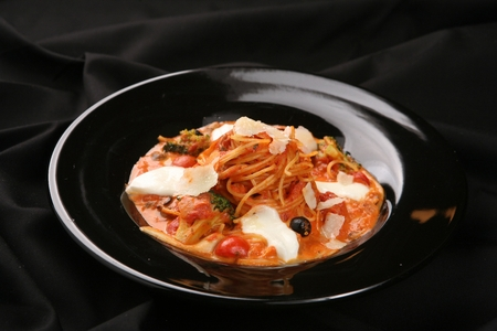Arrabiata pasta on a black plate, on a black tablecloth 免版税图像