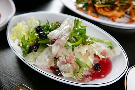 mini salad with greens, blueberry and dressing on white plate