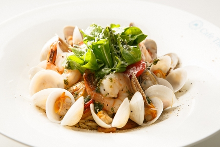 Vongole pasta with shrimp, on a white plate, close-up