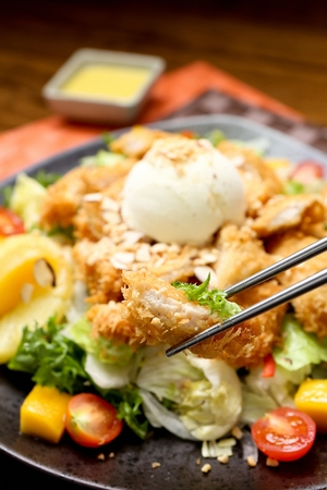 chicken salad with ice cream scoop, held with chopsticks, close-up shot