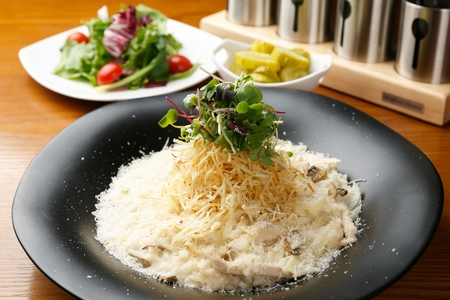 Chicken cream risotto with micogreens on a black plate, served beside a vegetable salad and pickles, on a table