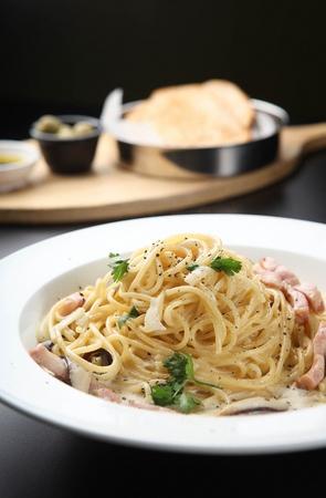 Gorgonzola cream pasta on a white plate, on a black table Banco de Imagens