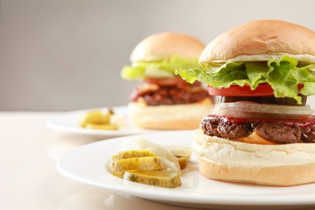 Handmade burgers on two white plates