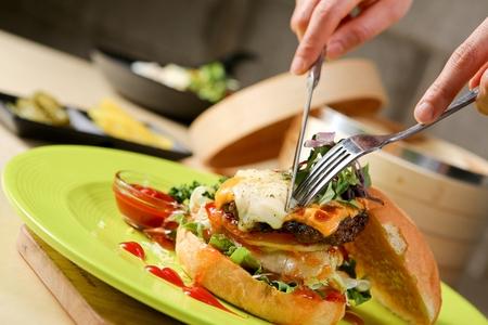 Hand cutting a handmade burger on a green plate