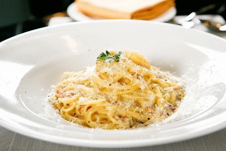 Pasta carbonara con queso espolvoreado, sobre una placa blanca.