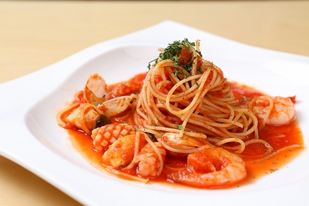 Pescatore tomato pasta on a white rectangular plate on a wooden table