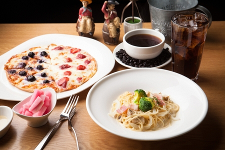 Carbonara pasta and pizza on a wooden table
