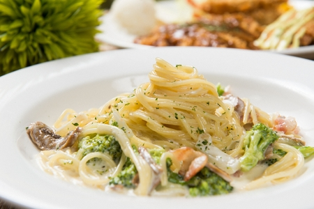 Broccoli carbonara pasta on a white plate, on a wooden table