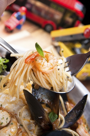 Fork lifting up a spicy chinese-style noodles pasta on a stainless plate, close-up