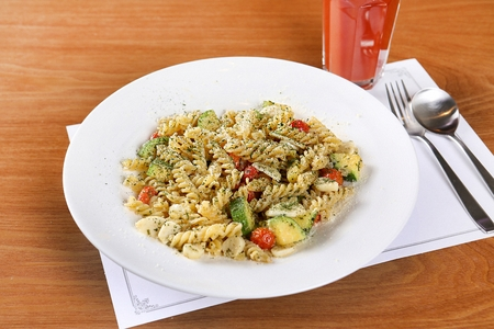 Pasta salad on a white plate, and a drink 免版税图像