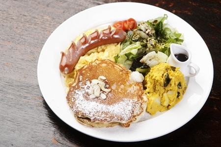 Sausage and pancake on a white round plate, on a wooden table Standard-Bild