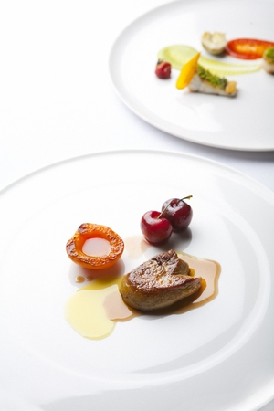 Foie gras on a white plate, on a white table Imagens