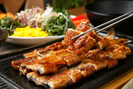 Grilled marinated eels on plate