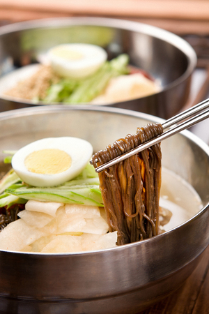 Chopsticks grabbing famous Korean cuisine, Mul Naengmyeon, buckwheat noodles served in chilled soup made of dongchimi (radish kimchi) and beef broth