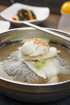 famous Korean cuisine, Mul Naengmyeon, buckwheat noodles served in chilled soup made of dongchimi (radish kimchi) and beef broth