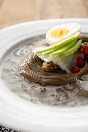 famous Korean cuisine, Mul Naengmyeon, buckwheat noodles served in chilled soup made of dongchimi (radish kimchi) and beef broth, close-up