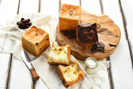 Bread with raisins, chocolate bread, knife on wooden cutting board