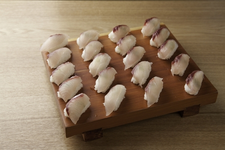Yellowtail sushi, a Japanese cuisine on a wooden cutting board